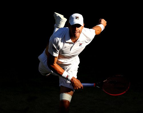 LONDON, ENGLAND - JULY 11:  John Isner of the United States serves against Milos Raonic of Canada during their Men's Singles Quarter-Finals match on day nine of the Wimbledon Lawn Tennis Championships at All England Lawn Tennis and Croquet Club on July 11, 2018 in London, England.  (Photo by Matthew Stockman/Getty Images)